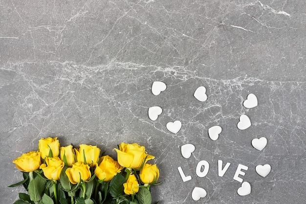 Rosas amarelas, palavra amor e corações brancos em cinza Foto Premium