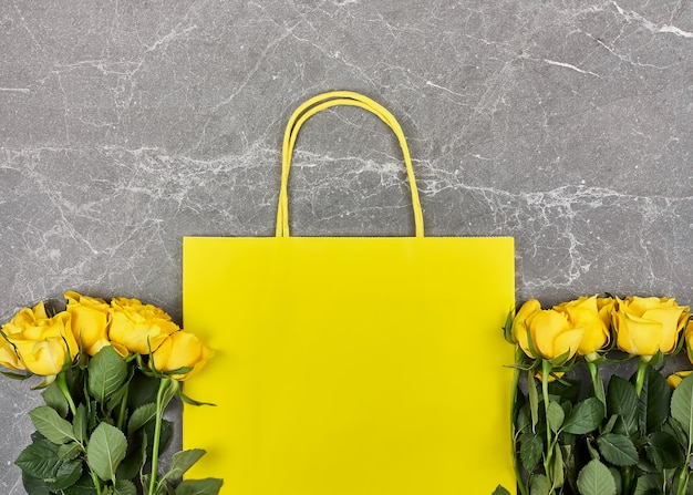 Rosas amarelas, saco de papel amarelo em cinza Foto Premium