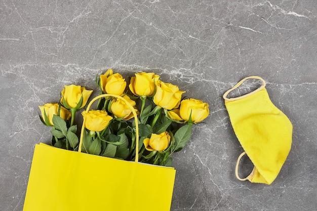 Rosas amarelas, saco de papel amarelo, máscara protetora amarela em cinza Foto Premium
