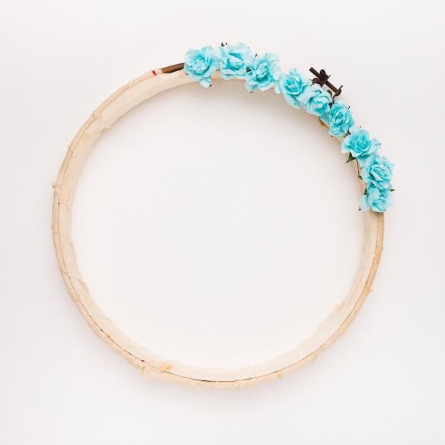 Rosas azuis na armação de borda circular de madeira no pano de fundo branco Foto gratuita