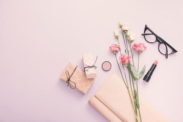 Rosas com caixas de presente e batom na mesa Foto gratuita