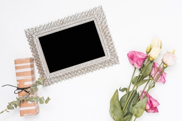 Rosas com moldura em branco e caixa de presente Foto gratuita
