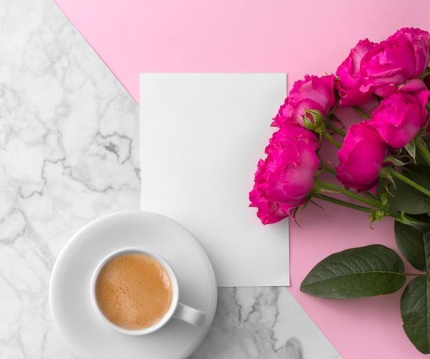 Rosas cor de rosa com cartão em branco e xícara de café sobre mármore rosa Foto Premium