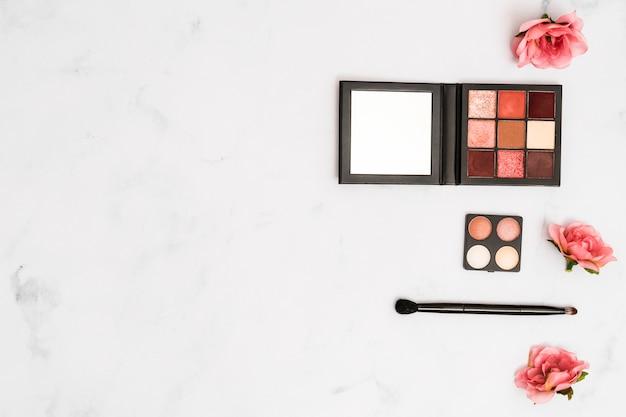 Rosas cor de rosa com pincel de maquiagem e paleta de sombra no fundo Foto gratuita