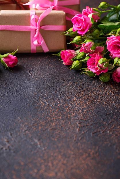 Rosas cor de rosa e caixas de presente com fitas Foto Premium