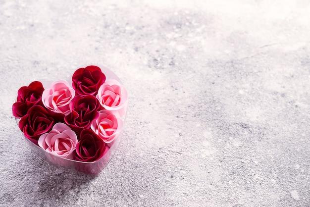 Rosas cor-de-rosa e vermelhas brilhantes feitas de aparas de sabão, em uma caixa em forma de coração. Foto Premium