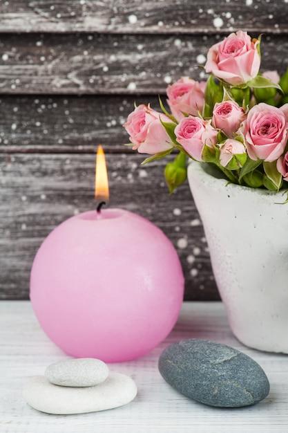 Rosas cor de rosa em vaso de concreto com vela Foto Premium