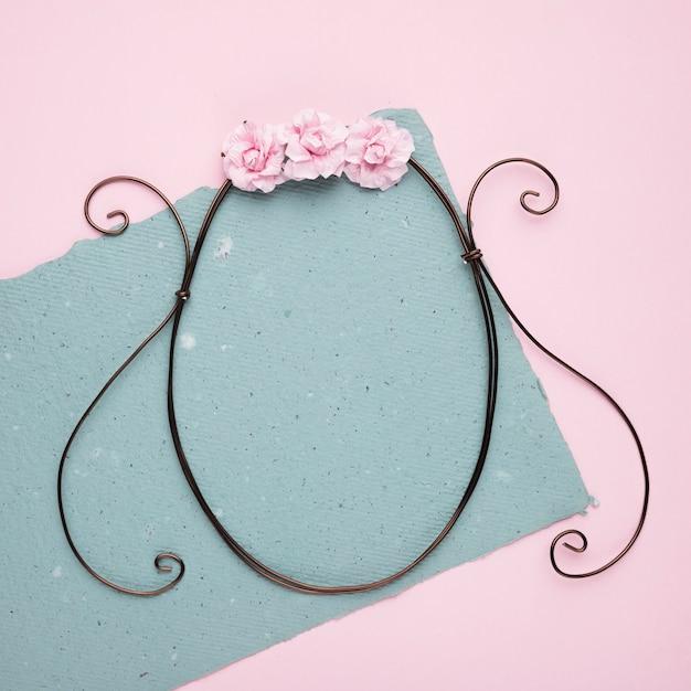Rosas cor de rosa na armação de metal vazia no papel sobre o pano de fundo-de-rosa Foto gratuita