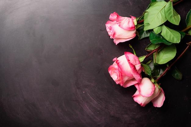 Rosas cor de rosa na lousa preta. feliz dia da mulher. conceito de dia dos namorados. presente para ela Foto Premium