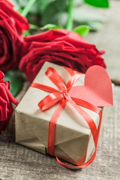 Rosas e um coração na placa de madeira, dia dos namorados Foto Premium