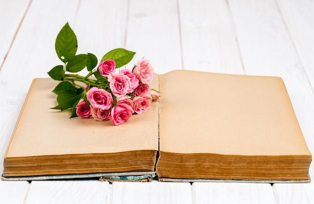 Rosas em um livro antigo sobre fundo branco de madeira. flores Foto Premium