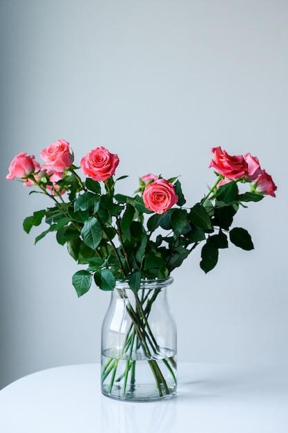 Rosas em um vaso transparente, sobre um fundo cinza com espaço para seu texto. Foto Premium