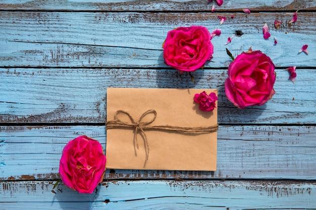 Rosas fofos e envelope vintage Foto gratuita