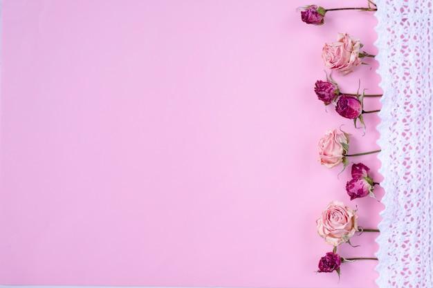 Rosas secas pequenas no fundo rosa pastel, Foto Premium