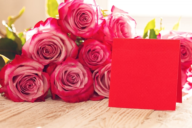 Rosas vermelhas com cartão vermelho em branco para dia dos namorados Foto Premium