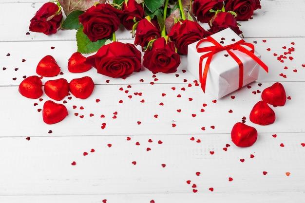 Rosas vermelhas e caixa de presente na mesa de superfície de madeira Foto Premium