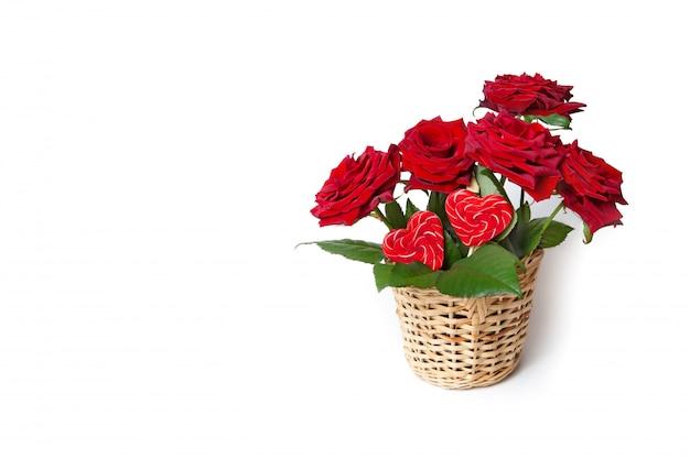 Rosas vermelhas e doces do coração em uma cesta de vime em um fundo isolado branco. cartão de felicitações Foto Premium