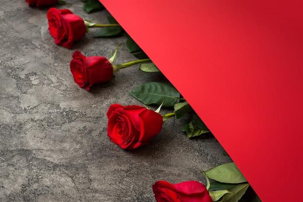 Rosas vermelhas e papel vermelho Foto Premium