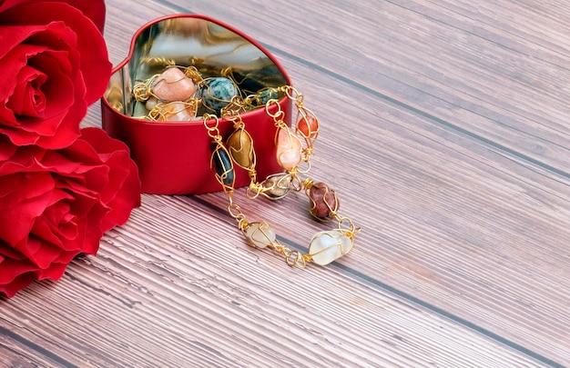 Rosas vermelhas e um recipiente de jóias em forma de coração Foto Premium