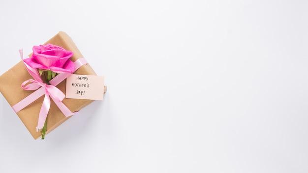 Rose com caixa de presente e inscrição feliz dia das mães Foto gratuita