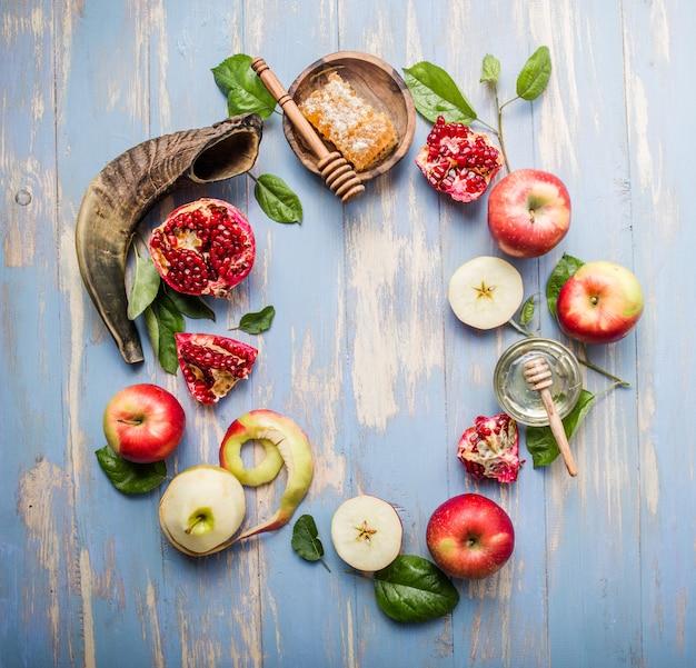 Rosh hashaná (hashana) - conceito de feriado de ano novo judaico. frasco de mel e maçãs frescas com romã e shofar - chifre sobre um fundo azul. copie o espaço para texto. vista de cima Foto Premium