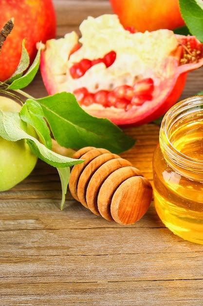 Rosh hashaná judeu conceito de feriado de ano novo. símbolo tradicional. maçãs, mel, romã. Foto Premium