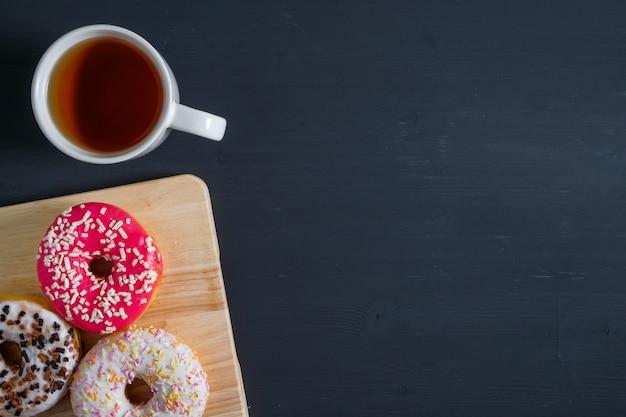 Rosquinhas de vidro branco, rosa e marrom com uma xícara de chá no lado esquerdo em madeira preta Foto Premium