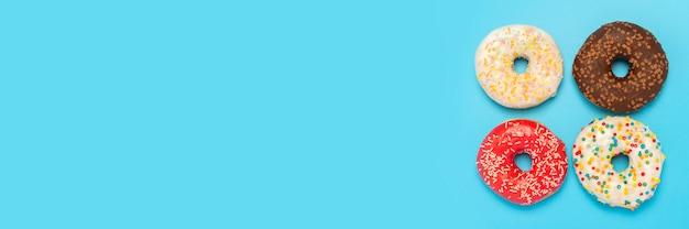 Rosquinhas saborosas de diferentes tipos em uma superfície azul. Foto Premium