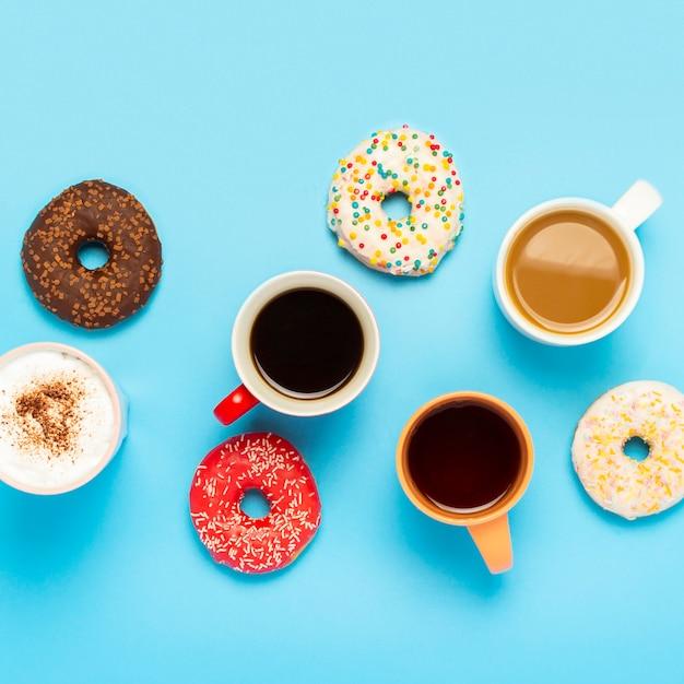 Rosquinhas saborosas e copos com bebidas quentes, café, cappuccino, chá sobre uma superfície azul. conceito de doces, padaria, bolos, café, reunião, amigos, equipe amigável. quadrado. vista plana, vista superior Foto Premium