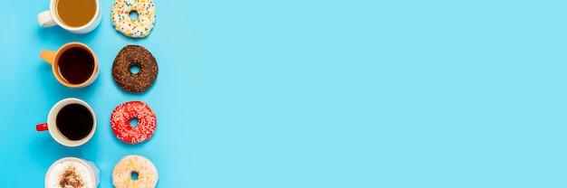 Rosquinhas saborosas e copos com bebidas quentes, café, cappuccino, chá sobre uma superfície azul. conceito de doces, padaria, bolos, café, reunião, amigos, equipe amigável. . vista plana, vista superior Foto Premium