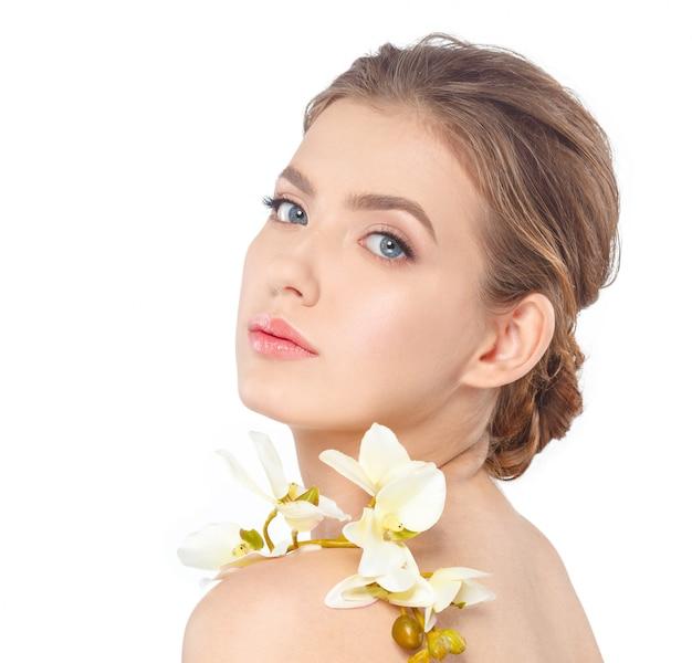 Rosto de beleza da jovem mulher bonita com flor Foto Premium