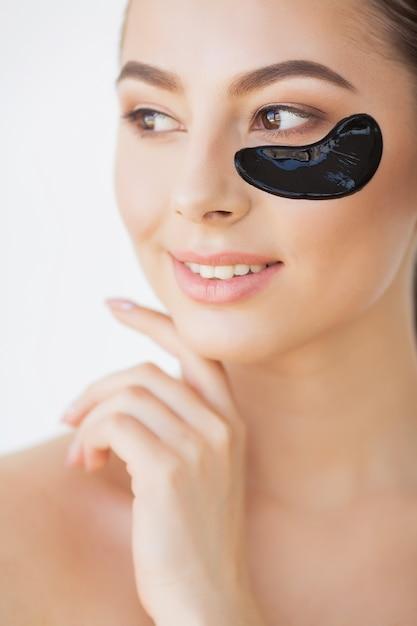 Rosto de beleza de mulher com máscara sob os olhos. mulher bonita com maquiagem natural e manchas de colágeno preto na pele facial fresca Foto Premium