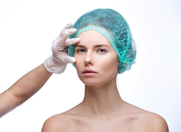 Rosto de exame médico de mulher bonita pelas mãos na luva - retrato de close-up isolado no branco Foto Premium