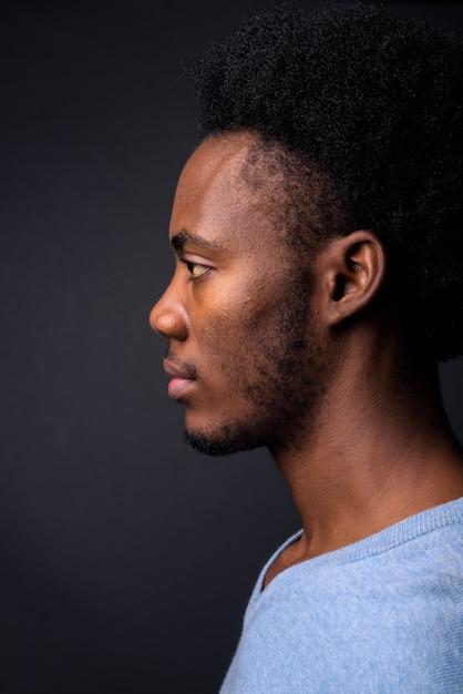 Rosto de jovem africano bonito contra um fundo cinza Foto Premium