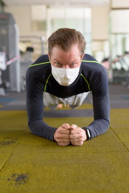 Rosto de jovem com máscara fazendo posição de prancha no chão na academia durante coronavírus covid-19 Foto Premium