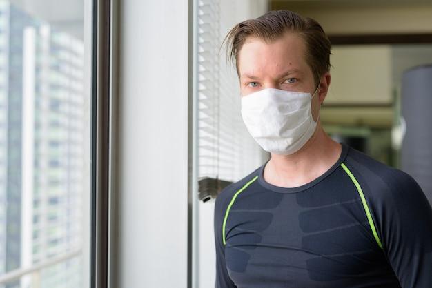 Rosto de jovem com máscara para proteção contra surto de coronavírus pronto para se exercitar durante covid-19 Foto Premium