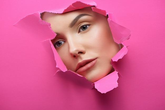 Rosto de menina bonita no buraco de papelão cor-de-rosa dilacerado. Foto Premium