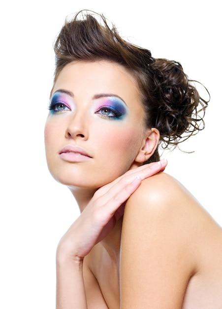 Rosto de mulher bonita com maquiagem brilhante e penteado criativo Foto gratuita