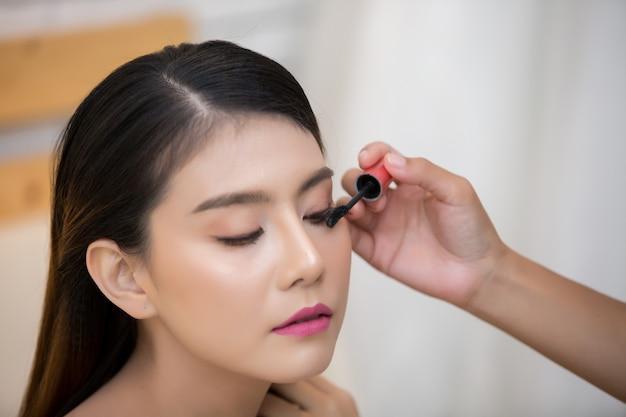 Rosto de mulher bonita e mão de maquiagem Foto gratuita