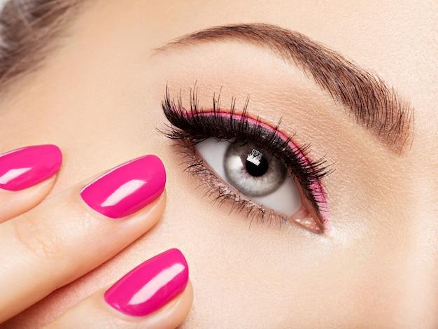 Rosto de mulher closeup com unhas rosa perto dos olhos. unhas com manicure rosa Foto gratuita