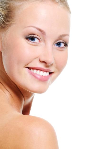 Rosto de mulher com um sorriso simpático e uma bela pele saudável e clara sobre fundos brancos Foto gratuita