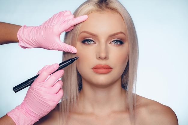 Rosto de mulher e mãos de médico com lápis, conceito de cirurgia plástica Foto Premium