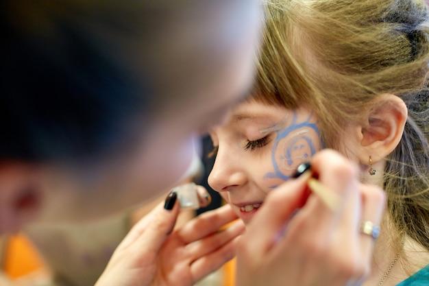 Rosto de mulher pintura de criança ao ar livre. pintura de rosto de bebê Foto Premium