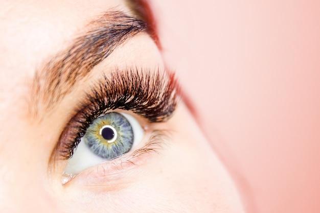 Rosto de mulher recortada com olho longo cílios postiços close-up Foto Premium