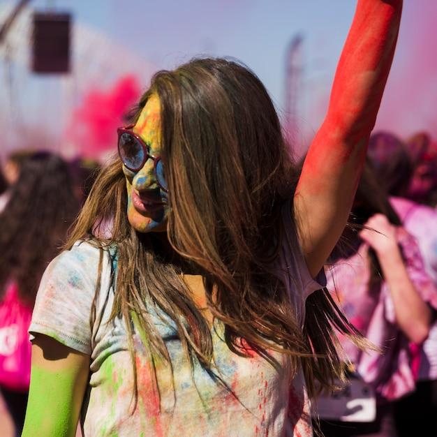 Rosto de mulheres jovens coberto com dança de cor holi Foto gratuita