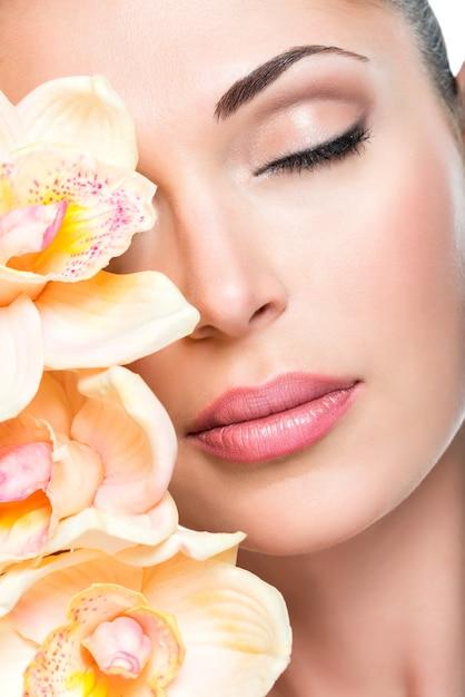Rosto lindo relaxado de uma jovem com pele clara e orquídeas cor de rosa. conceito de tratamento de beleza Foto gratuita