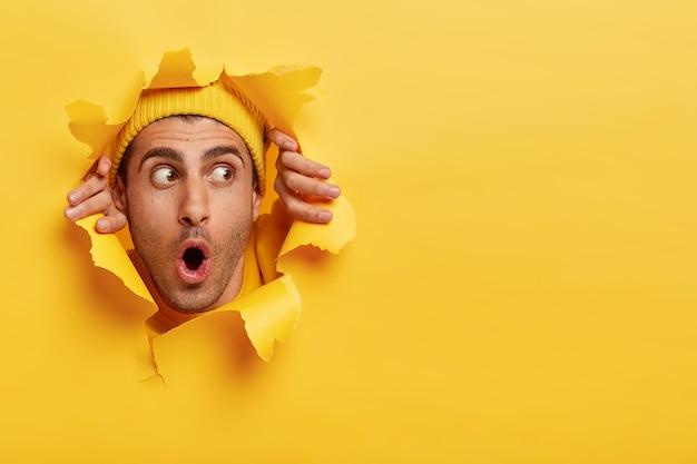 Rosto masculino surpreso pelo buraco do papel. jovem surpreso e emocional usando um capacete amarelo Foto gratuita