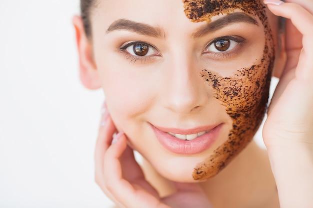 Rosto skincare. jovem garota charmosa faz uma máscara de carvão preta no rosto Foto Premium