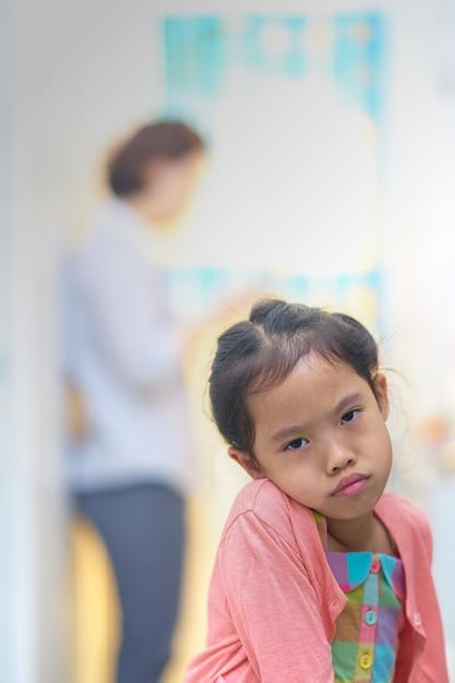Rosto triste ou com raiva pequena menina na mamãe ocupada no telefone inteligente Foto Premium