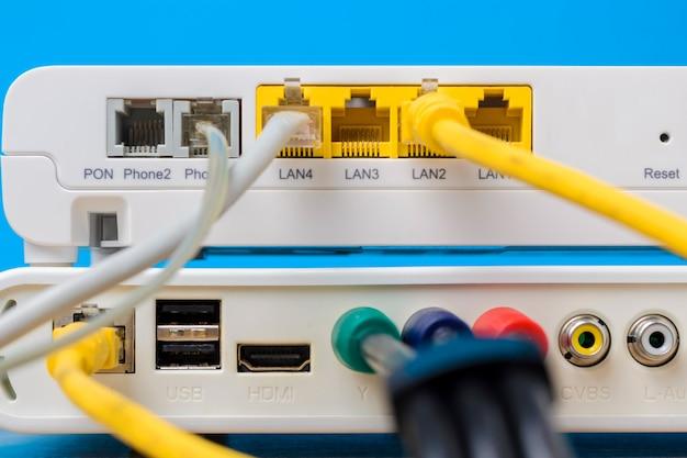 Roteador sem fio em casa com cabos ethernet plugged em fundo azul, close up Foto Premium